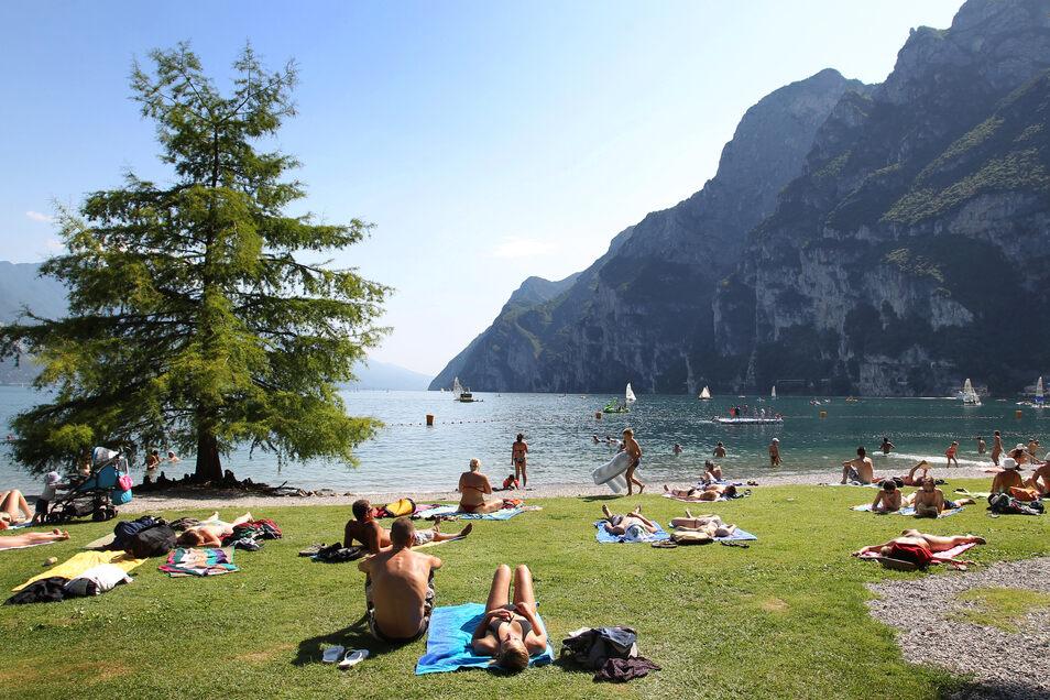 Touristen und Einheimische nehmen am Strand von Riva del Garda ein Sonnenbad. Reisen ist gut – für die Wirtschaft, aber vor allem für einen selbst.