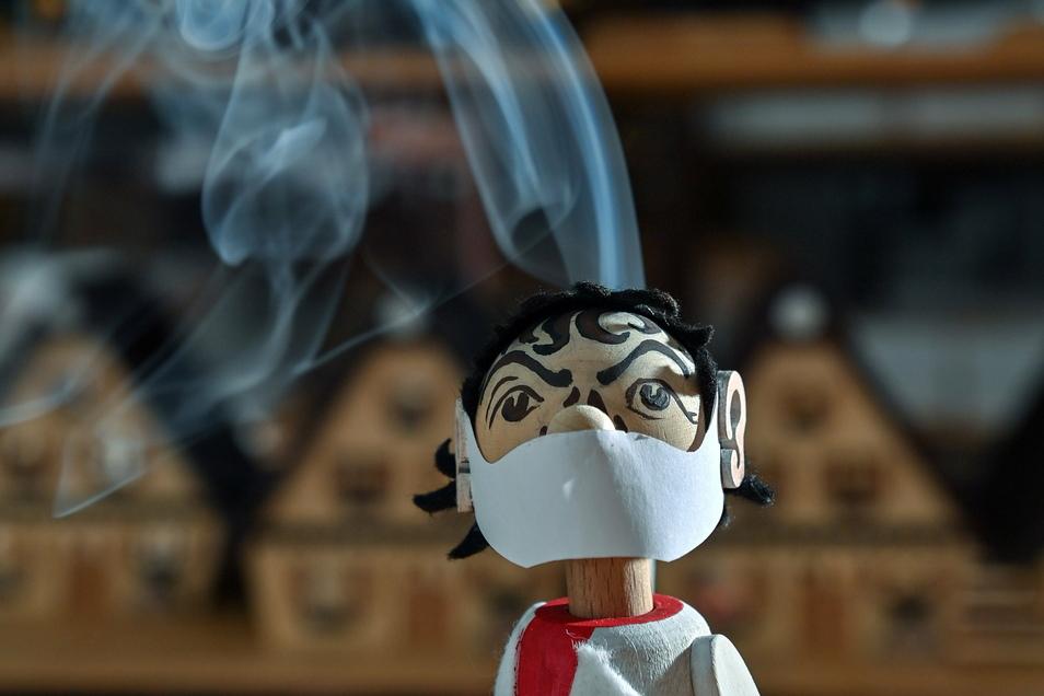 In der Werkstatt des Spielzeugmachers Tino Günther in Seiffen raucht der neuesten Figur des Sortiments der Kopf. Der Virologen-Räuchermann mit seinem Mund-Nasen-Schutz erinnert stark an den Charité-Virologen Drosten.