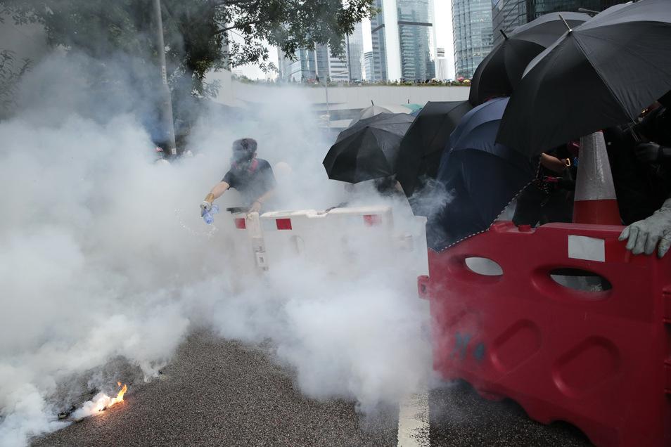 Ein Demonstrant schüttet Wasser über eine Tränengasgranate. Trotz des Verbots einer Großdemonstration kommt es in Hongkong erneut zu Protesten gegen die Regierung.