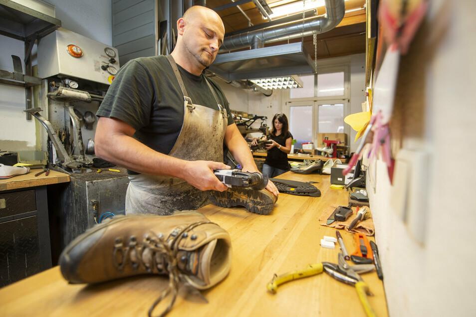 Schuhmacher Marcus Lange repariert Wanderschuhe in seiner Werkstatt in der Breite Straße 22 in Pirna. Im Hintergrund steht Mitarbeiterin Grit Rieger.