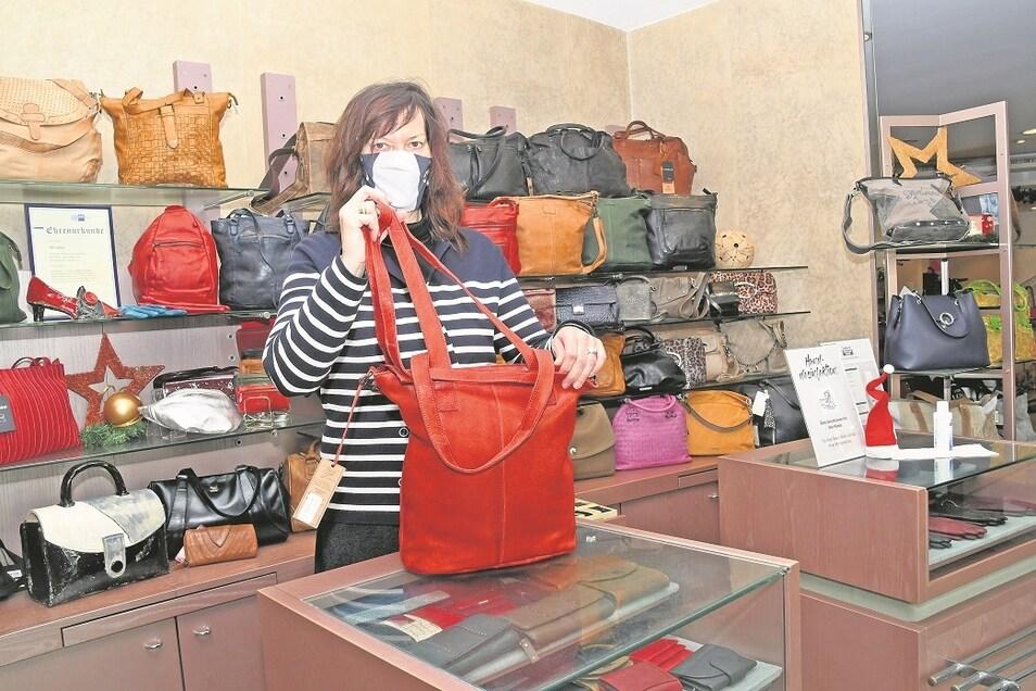 Fachverkäuferin Carmen Paukert stellt im Lederwaren Christian Hemmo eine der Taschen aus dem vielfältigen Angebot an Schuhen und Lederwaren vor. Das bekannte und alteingesessene Fachgeschäft konnte im Juli dieses Jahres auf sein 100-jähriges Bestehen in der Glasmacherstadt zurückblicken.