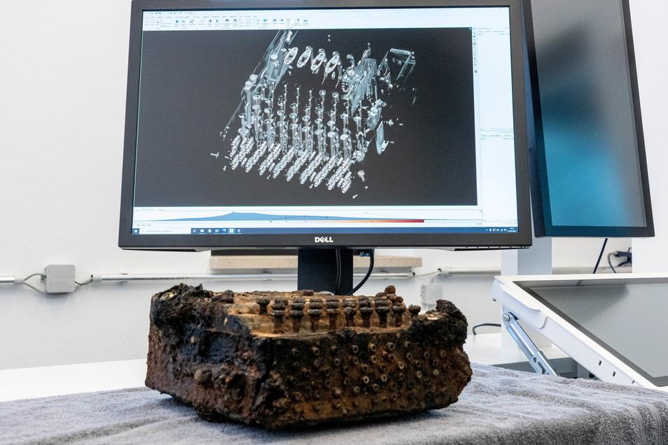Die Enigma-Verschlüsselungsmaschine, liegt vor dem Monitor eines Computertomographen aus der Medizintechnik, mit dem eine 3D-Ansicht des Gerätes erzeugt wurde.