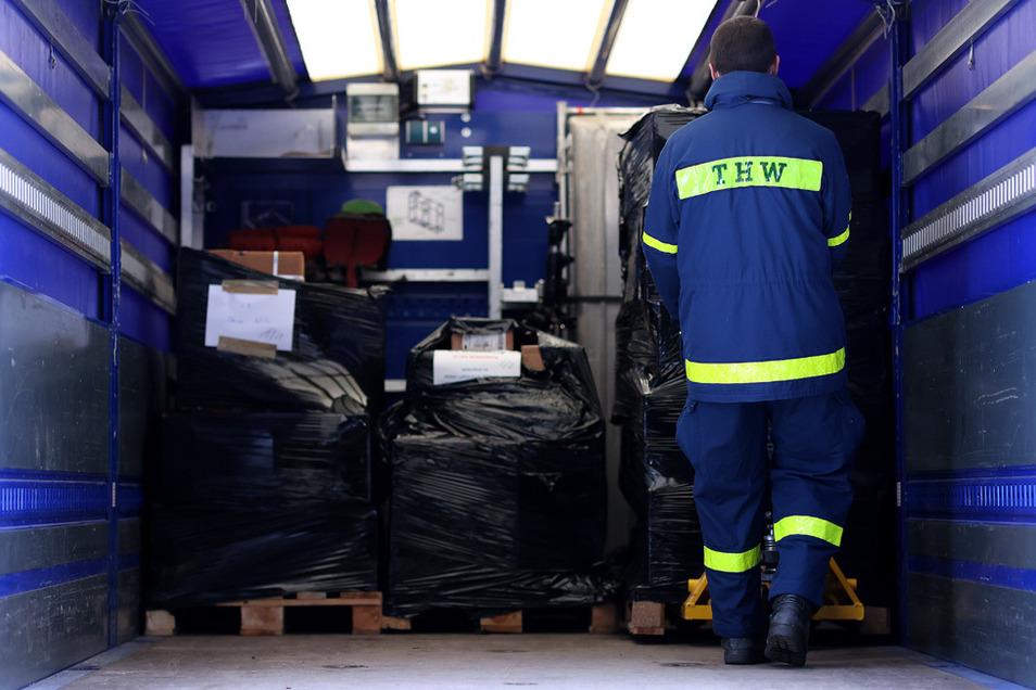 Ein Mitarbeiter der Bundesanstalt Technisches Hilfswerk (THW) belädt in einem Impfstofflager einen LKW mit medizinischem Material.