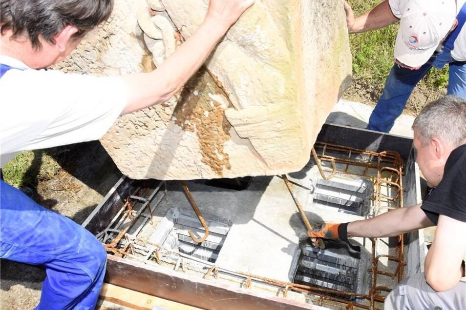 Vorsichtig werden die Stahlklammern in die vorbereiteten Fundamentlöcher eingesetzt.