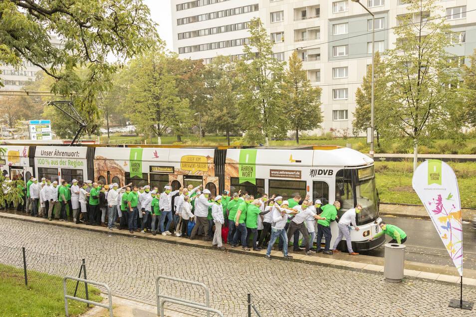 20 Landwirte, 20 Bäcker und Verterter der Dresdener Mühle schieben die neue Straßenbahn an.