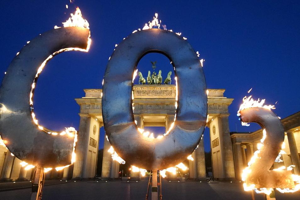 Bei einer Greenpeace-Aktion steht ein CO-2 Schriftzug vor dem Brandenburger Tor in Berlin, aus dem Flammen schlagen.