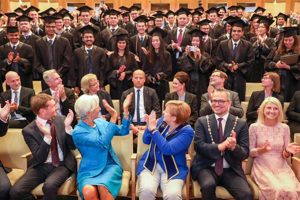 Merkel, Lagarde und Kretschmer beglückwünschen die Absolventen der Leipziger Handelshochschule.