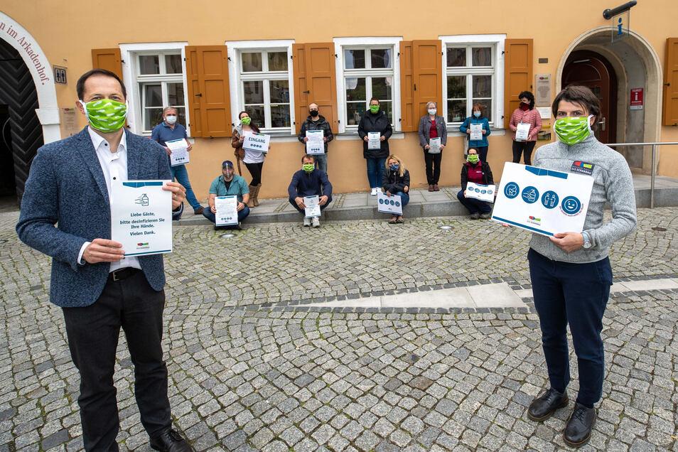 Bürgermeister Thomas Kunack (li.), Tourismuschefin Gundula Strohbach (re.) und Bad Schandauer Vermieter mit Hinweisschildern im Design der Stadt.