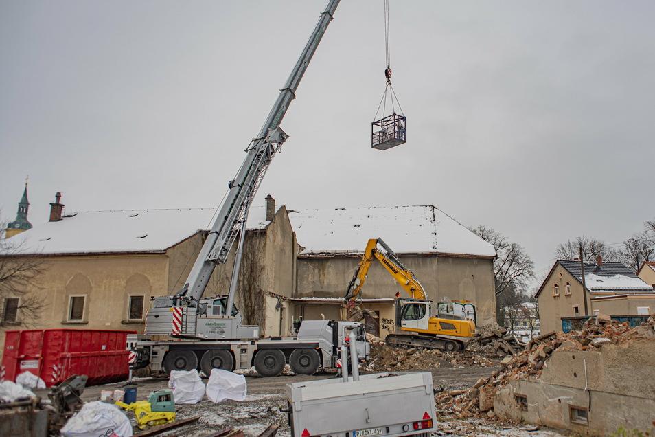 Der Abriss der Kante in Pulsnitz ist gestartet. Mit einem Kran werden Bauleute an das Gebäude gebracht.