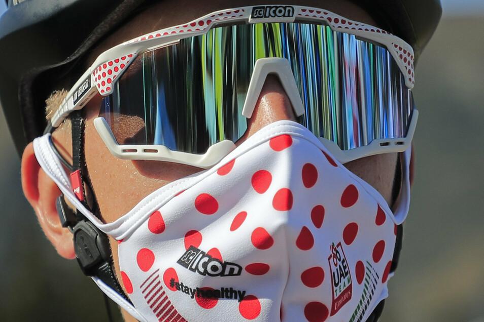 Tadej Pogacar aus Slowenien vom Team Emirates trägt, passend zu seinem rot-gepunktetem Trikot, eine Maske mit dem gleichen Design.Doch außer der Bergwertung hat er nun auch den Gesamtsieg vor Augen.