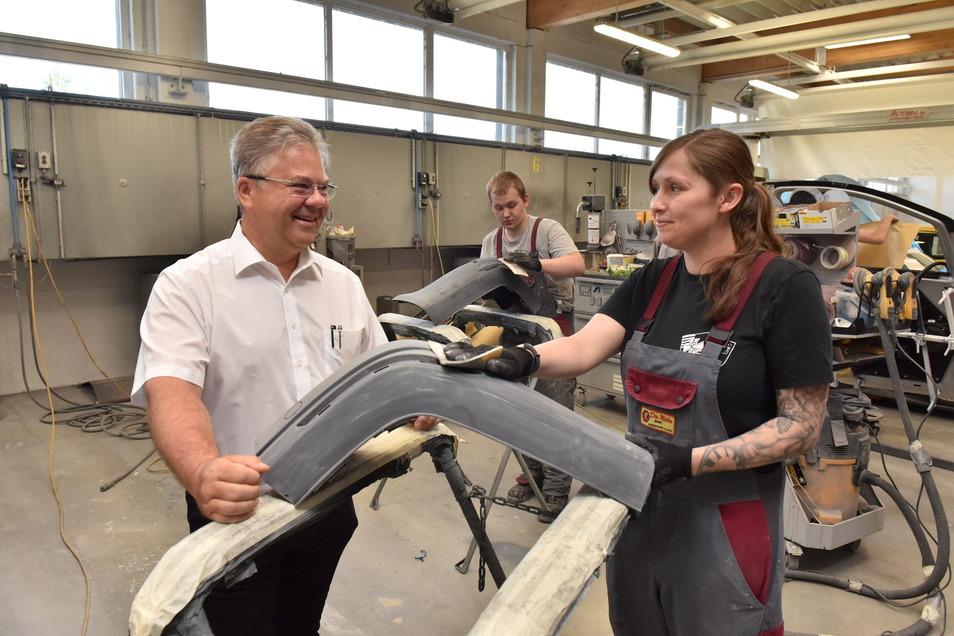 Geschäftsführer Mario Schneider bespricht mit den Lackierer-Lehrlingen Elisa Zschieschang und Nico Weißleder, was zu tun ist.