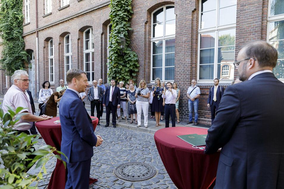 Ministerpräsident Michael Kretschmer (vorn, Mitte) bei der Übergabe der Fördermittel aus dem DigitalPakt. Mehrere Schulleiter waren zu dem Termin im Hof der Görlitzer Fischmarktschule gekommen.