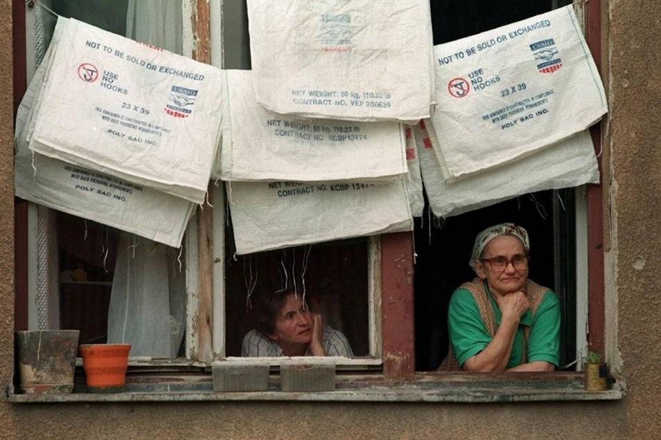 Im Mai 1996 blicken zwei bosnische Flüchtlingsfrauen in einem Flüchtlingslager in Sarajevo aus dem Fenster.