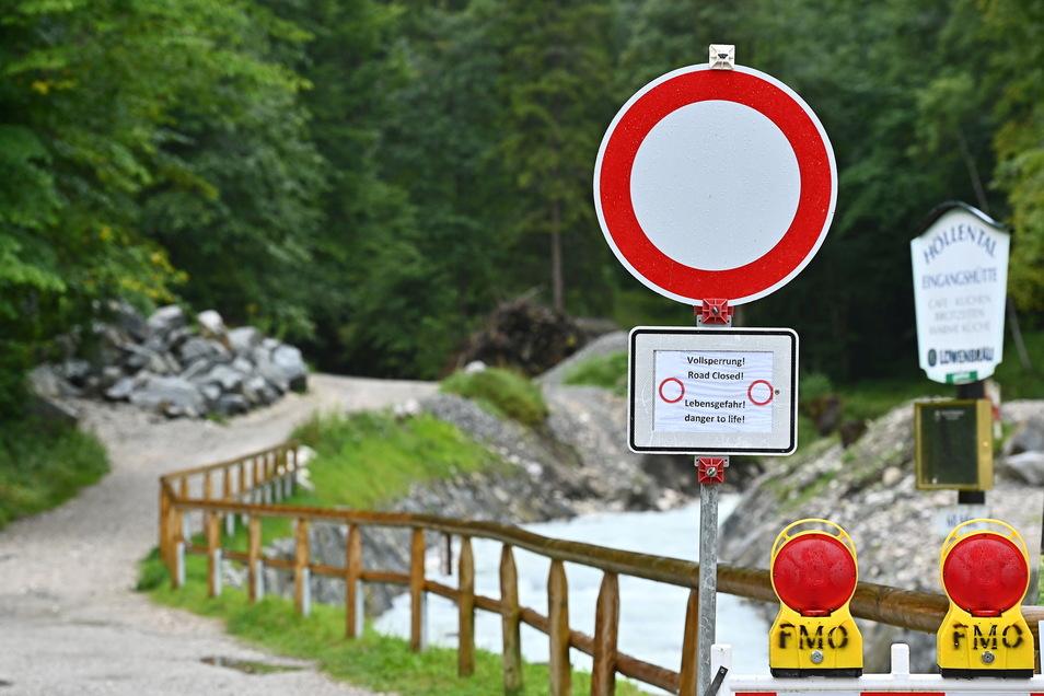 Ein Schild mit der Aufschrift ·Vollsperrung! Lebensgefahr!· steht am Eingang zur Höllentalklamm. Nach der Flutwelle in der Klamm an der Zugspitze geht die Suche nach zwei Vermissten weiter.