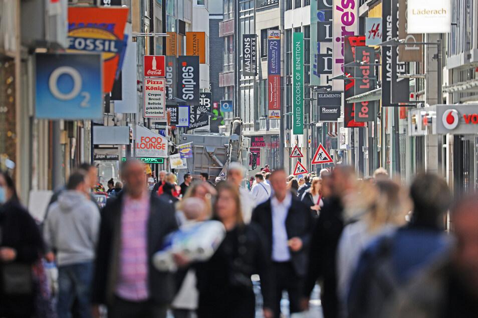 Zahlreiche Menschen gehen in Köln über die Einkaufsstraße Hohe Straße, auf der wieder etliche Geschäfte geöffnet haben. Bund und Länder hatten sich darauf verständigt, Geschäften bis zu 800 Quadratmetern Verkaufsfläche die Öffnung zu erlauben.