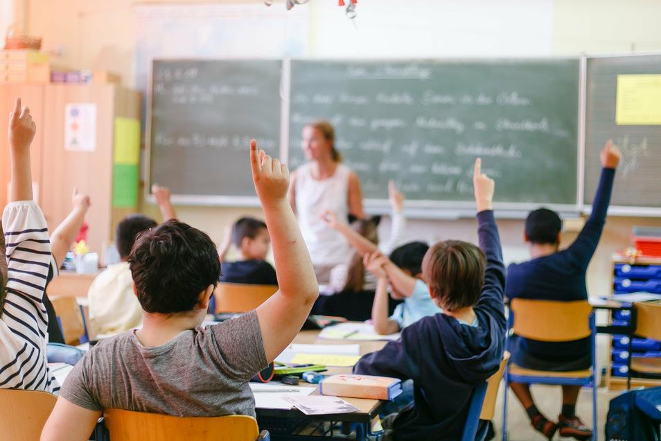Viertklässler einer Grundschule melden sich während des Unterrichts.