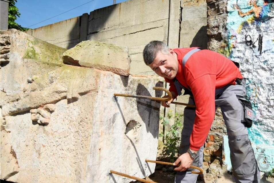 Marcel Reichel prüft, ob die Stahlklammern zur Befestigung des Klotzes am neuen Standort auch fest sitzen. Er ist ist der Betreiber des privaten Bunkermuseums auf dem Großenhainer Flugplatz. Hier erhält das  Denkmal seinen neuen Standort.