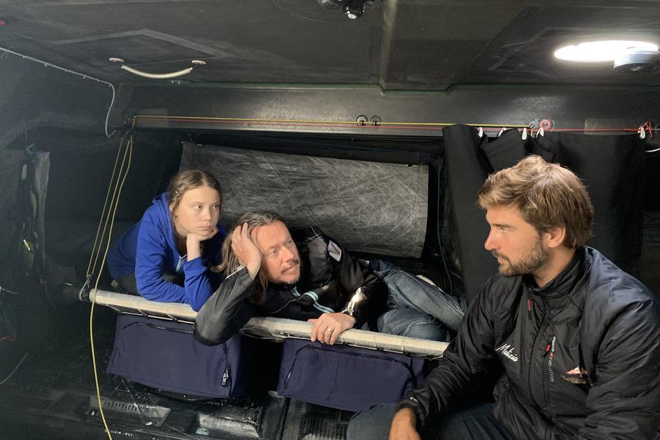 Greta Thunberg (-r), Klimaaktivistin aus Schweden, ihr Vater Svante Thunberg und Profisegler Boris Herrmann an Bord der Hochseejacht Malizia.