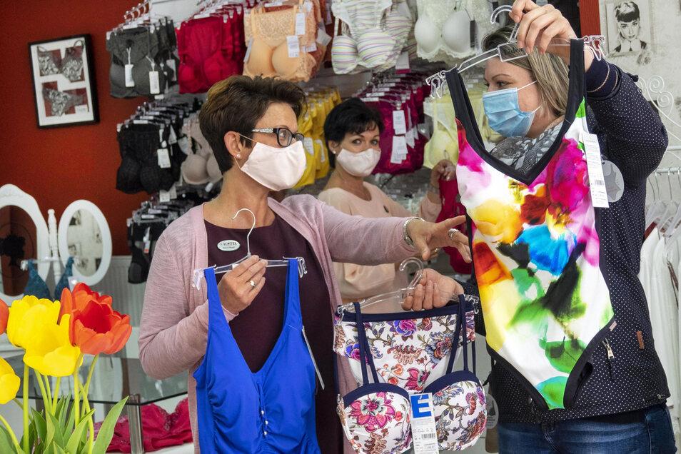Bei Calotta Dessous an der Hauptstraße berät Inhaberin Simone Bieder (l.) Kundin Sarah Franz (r.). Im Hintergrund Mitarbeiterin Romy Röthig. Die meisten in Riesa halten sich an die Maskenpflicht in den Geschäften.