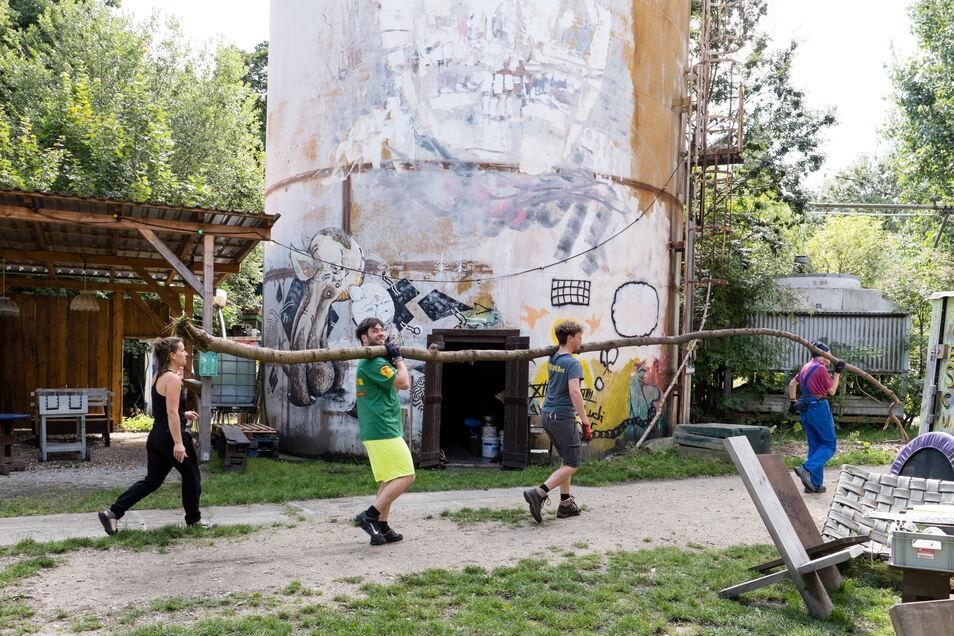 Das Rabryka-Gelände wird fürs Fokus-Festival vorbereitet. Um einen Baumstamm zu tragen, braucht es mehrere Leute.