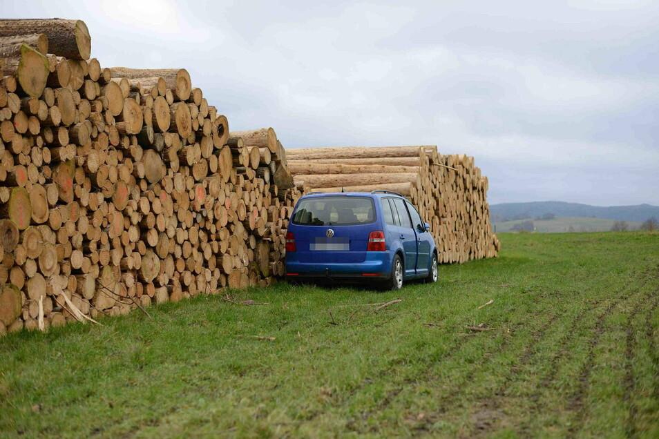 Der VW Touran hat hinter einem Holzstapel gestanden.