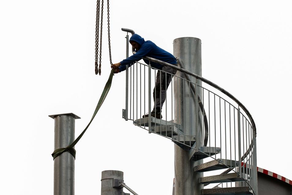 Der Monteur ist der erste Mann auf der Treppe zur Rutsche. Er löst die Gurte von einer zwei Säulen, die der Kranfahrer gerade abgesetzt hat und auf denen das Podest montiert wird.