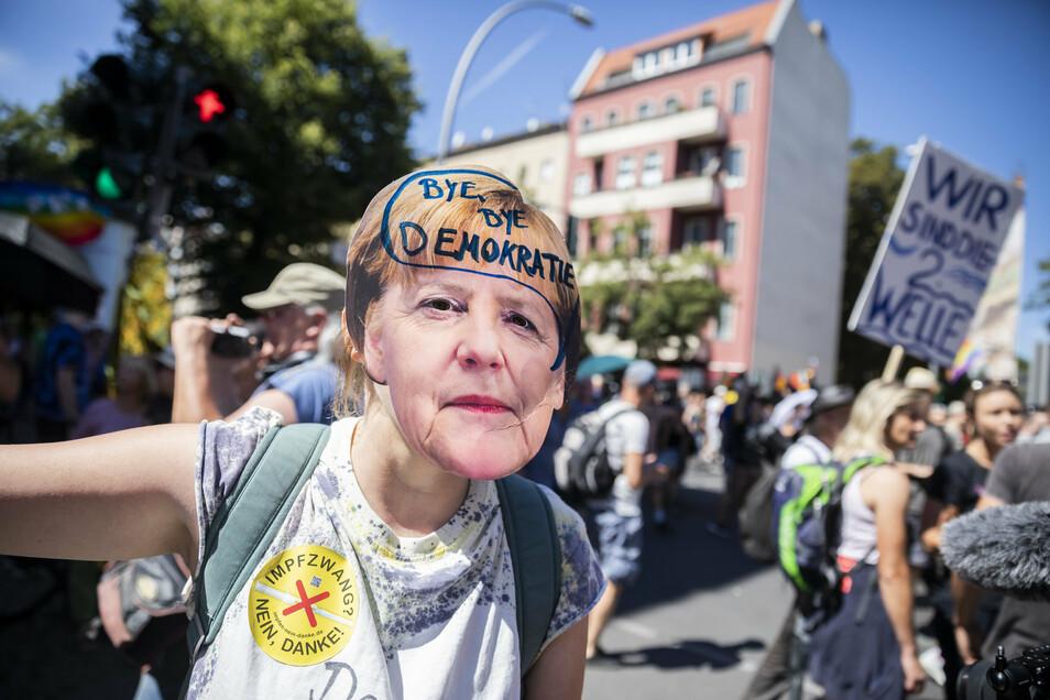 """Bei einer Demonstration in Berlin trägt ein Frau eine Merkel-Maske mit der Aufschrift """"Bye bye Demokratie""""."""