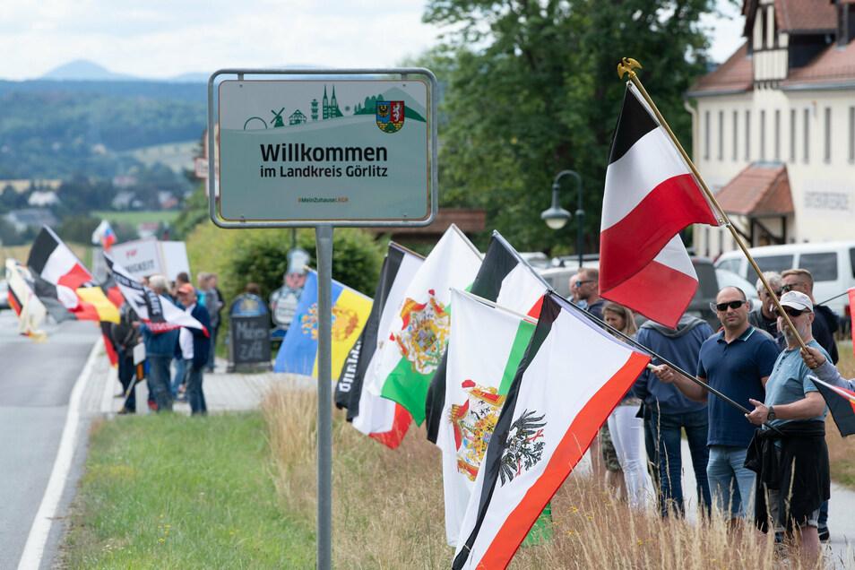 Teilnehmer eines Protests stehen mit Fahnen an der Bundesstraße 96. Die sogenannten B 96-Proteste richten sich unter anderem gegen die vermeintliche Überregulierung des Staates in Coronazeiten.