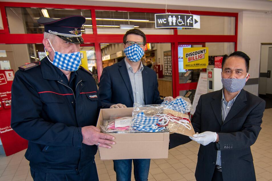 """Der Döbelner Wehrleiter Thomas Harnisch (links), Bürgermeister Sven Liebhauser und Phan Hop (rechts), Vorsitzender des Vereins """"Vietnamesen in Döbeln"""", zeigen einen Karton mit Gesichtsmasken, der für die Döbelner Feuerwehr bestimmt ist."""