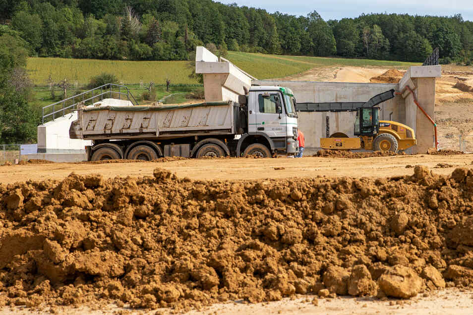 Ein Lkw kippt Erde ab und eine Walze fährt im Anschluss darüber.  Auf der Südumfahrung in Pirna wird derzeit der Boden vom Kohlberg für den Aufbau der Tragschicht verwendet.