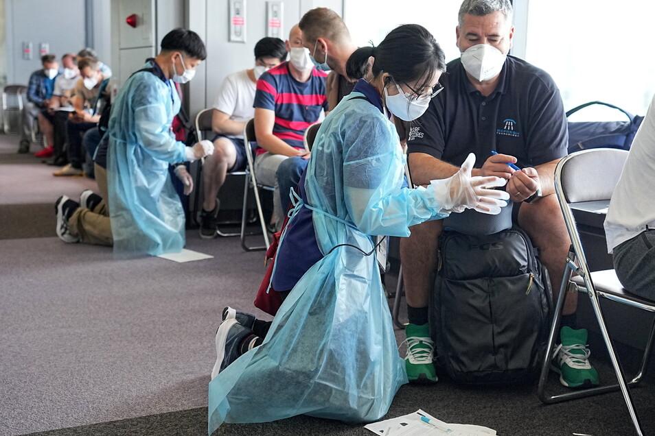 Am Flughafen Narita helfen Volunteers den anreisenden Olympia-Beteiligten bei den Einreiseformalitäten und kontrollieren die Dokumente.