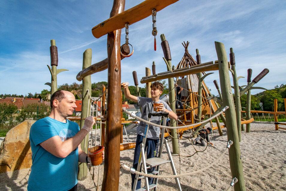 """Mitglieder des Vereins Osiris, hier Jens Gießmann und Tim Janke (von links), streichen die Spielgeräte auf dem Spielplatz """"Rösser im Schilf"""" in Roßwein"""