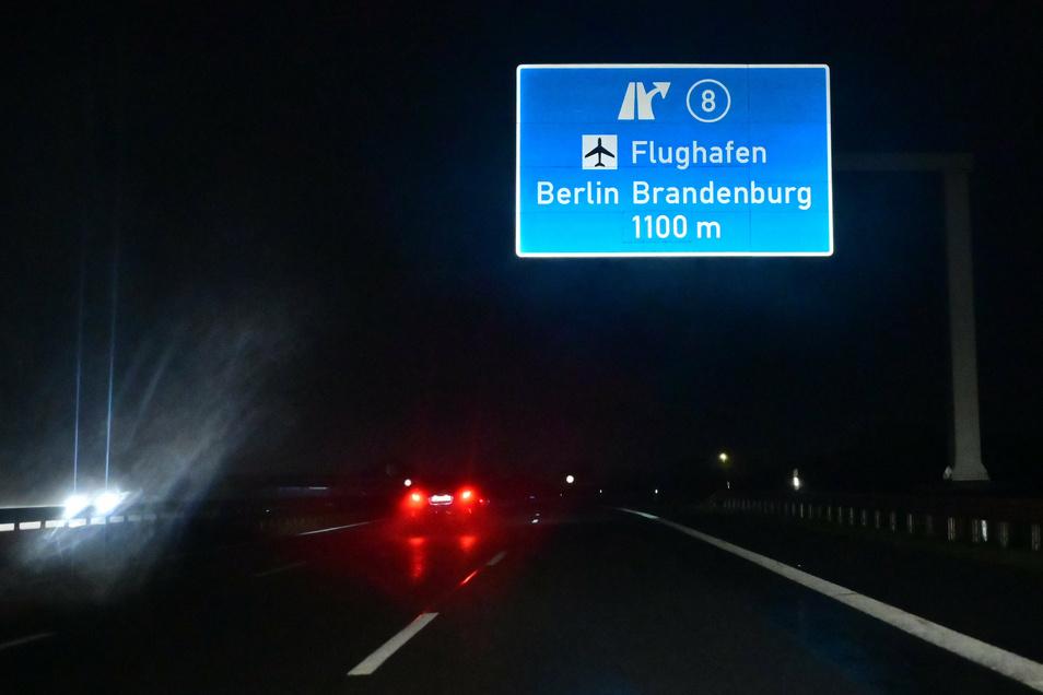 Im Licht der Autoscheinwerfer leuchtet am frühen Samstagmorgen ein Hinweisschild für eine Autobahnabfahrt zum Flughafen Berlin Brandenburg.