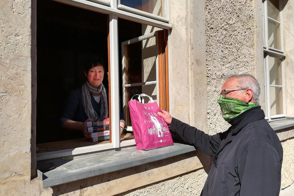 Literatur aus dem Fenster: Eine Mitarbeiterin der Stadtbibliothek reicht einem Interessierten einen Medienbeutel durch das geöffnete Fenster.