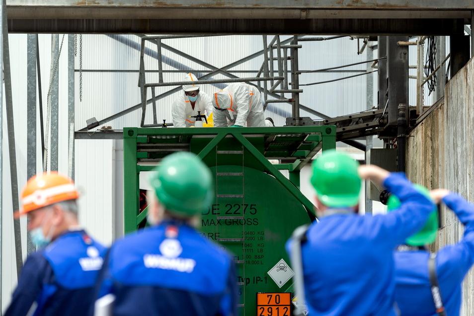 Begehrtes Fotomotiv: Nach dem Einfüllen der Uran-Suspension reinigen Mitarbeiter der Königsteiner Wismut in Schutzanzügen die Außenseite des Transportcontainers.