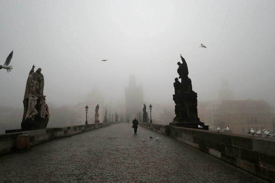 Ein Mann geht bei Nebel über die mittelalterliche Karlsbrücke. Die tschechische Regierung will die restriktiven Maßnahmen inmitten eines Anstiegs der hochansteckenden Coronavirus-Variante weiter verschärfen.