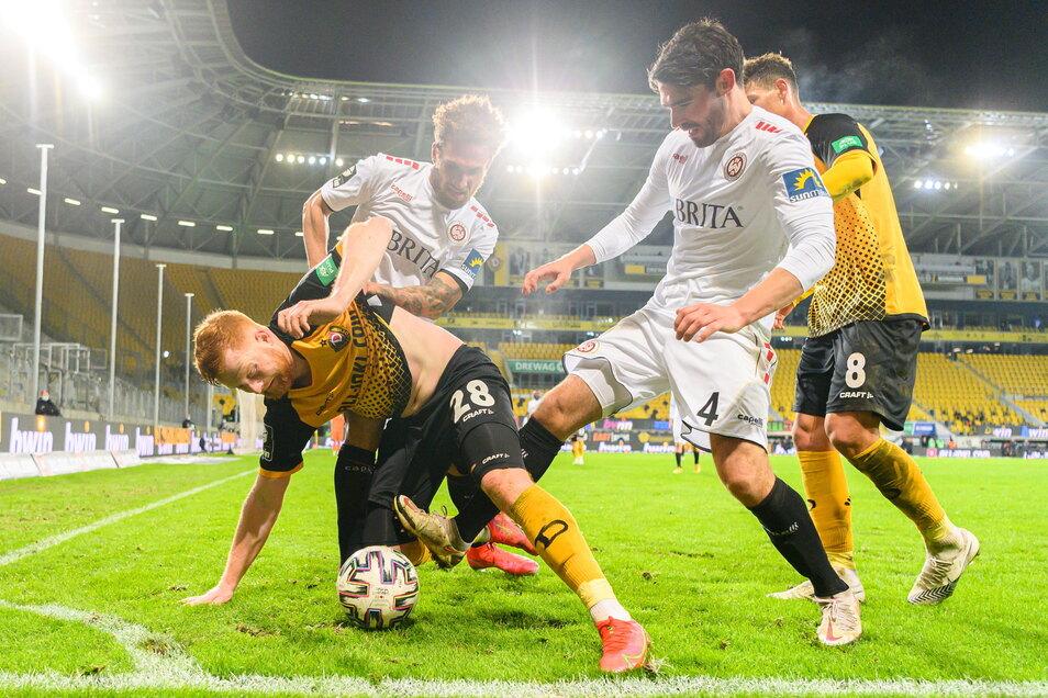 Es ist ein Kampfspiel - Dynamos Paul Will (l.) und Heinz Mörschel (r.) behaupten den Ball gegen Wiesbadens Sascha Mockenhaupt (2. v. r.) und Kevin Lankford.
