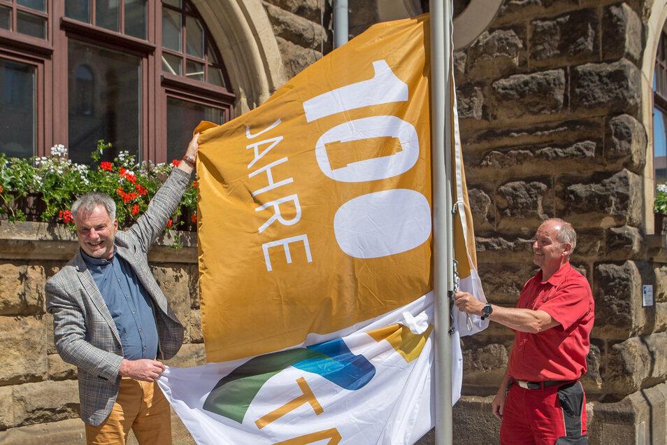 Oberbürgermeister Uwe Rumberg (links) und Hausmeister Hans-Joachim Huth hissen die neue Flagge.