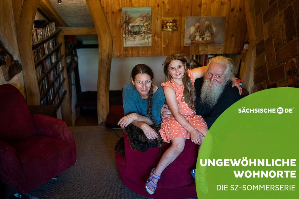 Doreen Stopporka (45), Jürgen Bergmann (64) und die gemeinsame Tochter Jolanda (7) sitzen in ihrem Wohnzimmer auf der Kulturinsel Einsiedel. Im Hintergrund ist die Kinoleinwand zu sehen. Sohn Janko (15) war zum Fototermin noch nicht zu Hause.