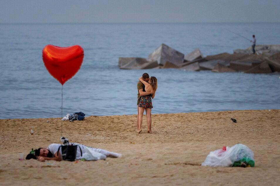 Spanien, Barcelona: Ein Paar küsst sich am Strand. Die Pandemie-Lage in Spanien bleibt entspannt.