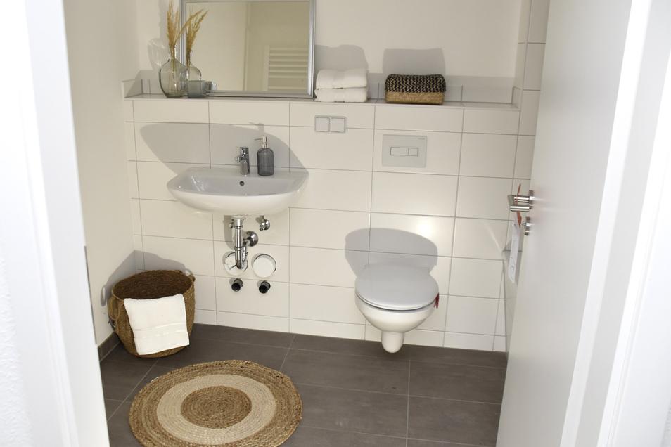 Ohne viel Schnickschnack, gefliest in grau und weiß: Im großen Bad gibt es eine Badewanne, in einem kleineren nur ein WC.