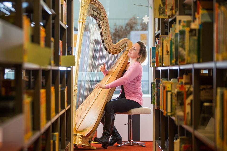 Mozart zwischen Bücherregalen: Sarah Christ erweckt die verwaiste Bibliothek im Kulturpalast mit Harfenklängen zum Leben.