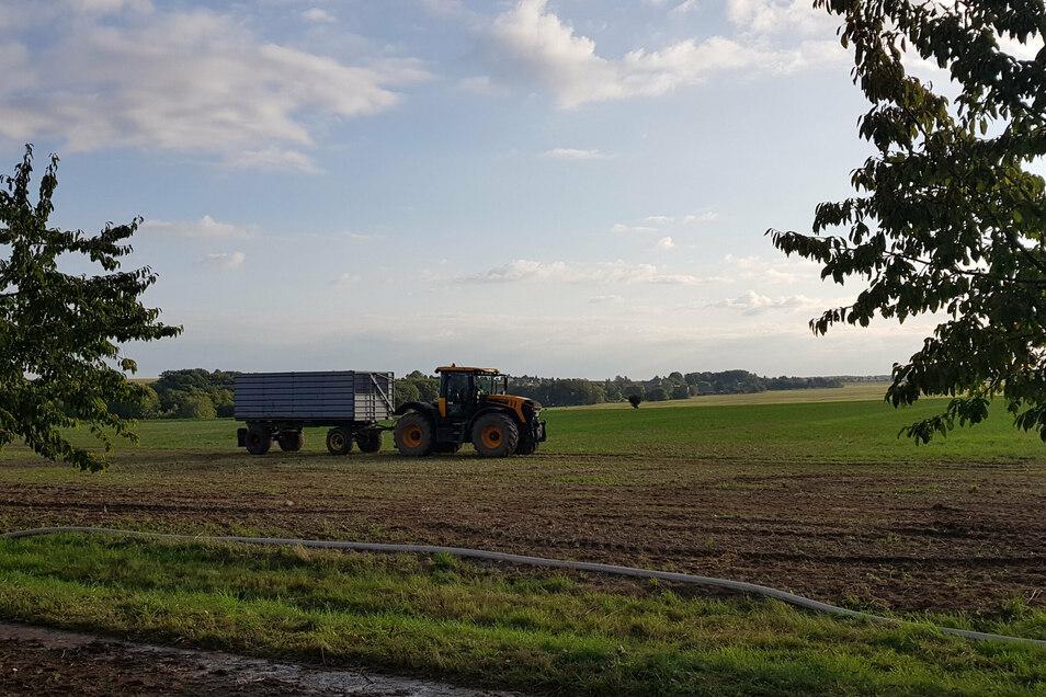 Mitarbeiter der Grünlichtenberger Agrargenossenschaft fahren das gelöschte Stroh auf das benachbarte Feld auf der gegenüberliegenden Straßenseite.
