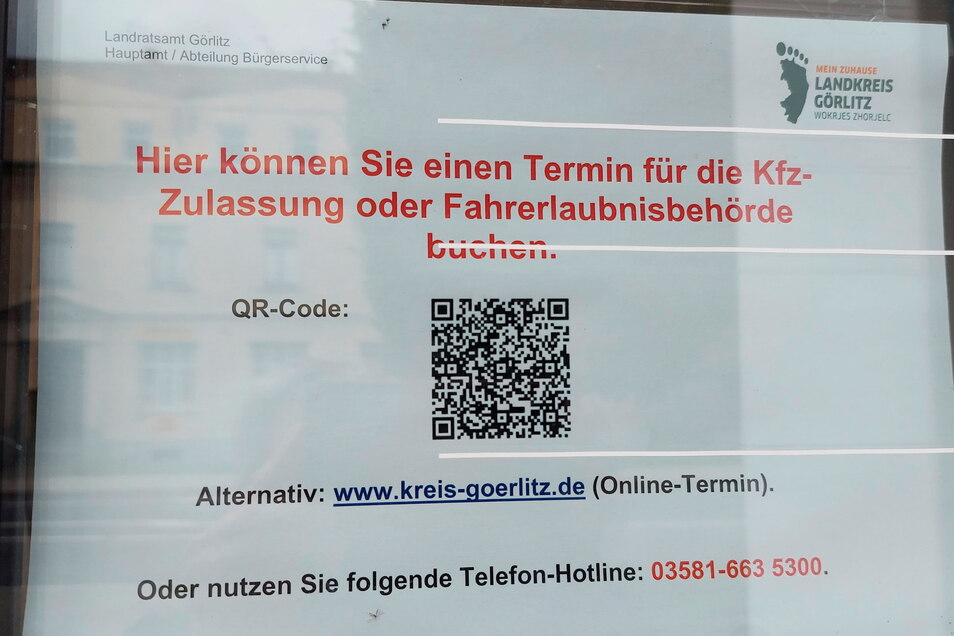 Auf einem zweiten Schild, das an der verschlossenen Tür hängt, wird auf die Online-Terminbuchung und die Hotline hingewiesen.