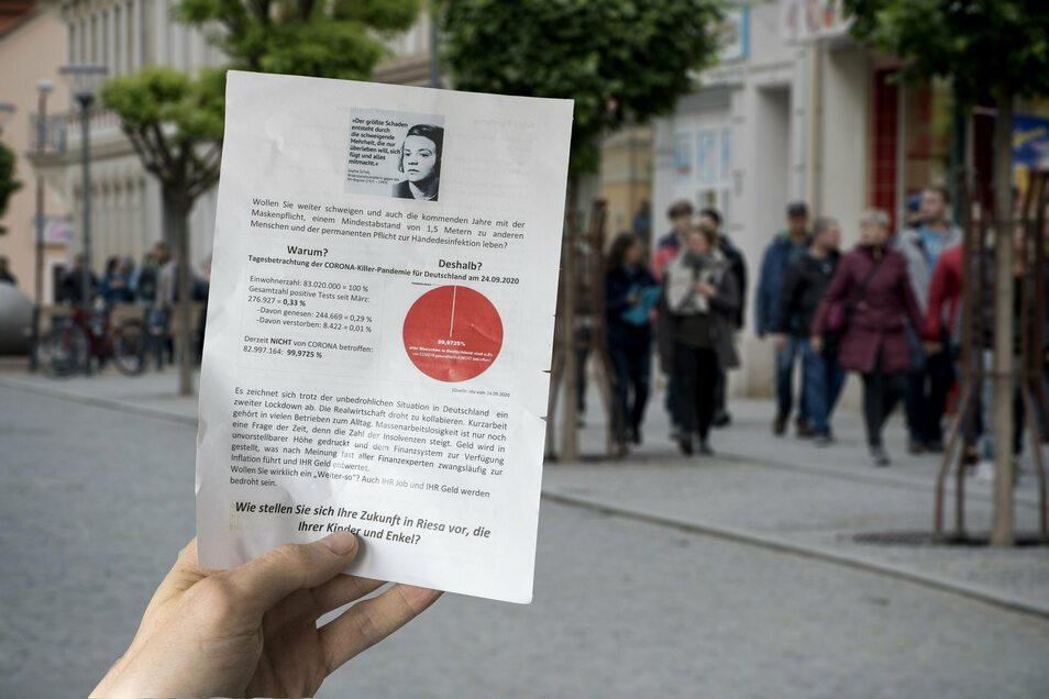 """Mit diesem Flugblatt haben offenbar Teilnehmer der montäglichen Corona-Proteste aufgerufen, sich ihnen anzuschließen. Das Foto im Hintergrund zeigt einen der ersten """"Spaziergänge"""" im Mai dieses Jahres."""