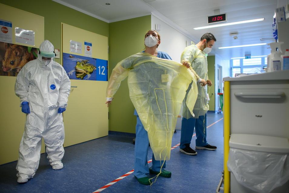Soldaten des Sanitätsdienstes der Bundeswehr ziehen sich auf der Corona-Station im Städtischen Klinikum Görlitz ihre Virenschutzkittel an.