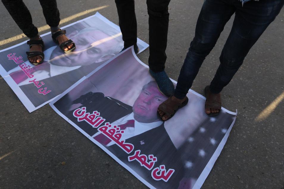 Palästinensische Demonstranten stehen auf Plakaten mit Bildern von US-Präsident Trump (r) und Israels Ministerpräsident Netanjahu bei einem Protest gegen Trumps Nahost-Plan. Auch die EU lehnt die US-Vorschläge ab.