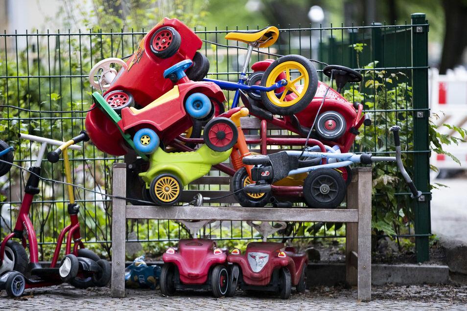 Symbolbild: Bobby-Cars, andere Spielautos und Gefährte für Kinder liegen angeschlossen vor einer Kita auf einem Stapel. Wie im Außenbereich Kinder getrennt werden, wird je Döbelner Kita individuell organisiert.