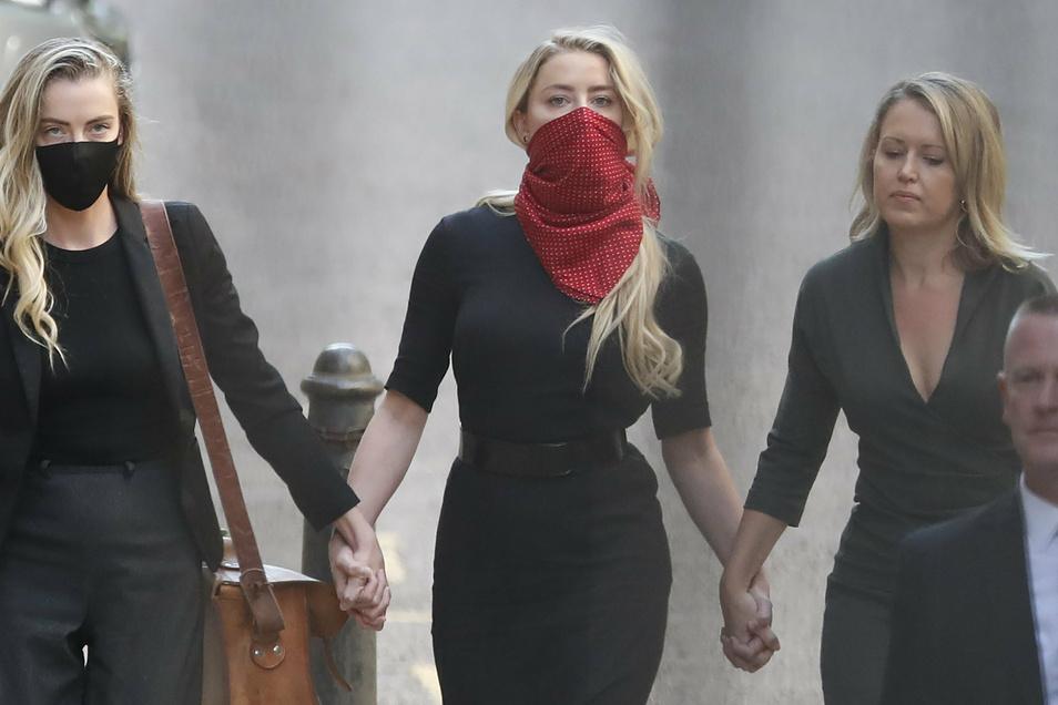 Amber Heard (M), Schauspielerin aus den USA, trifft mit ihrer Schwester Whitney Heard (l) am High Court ein.
