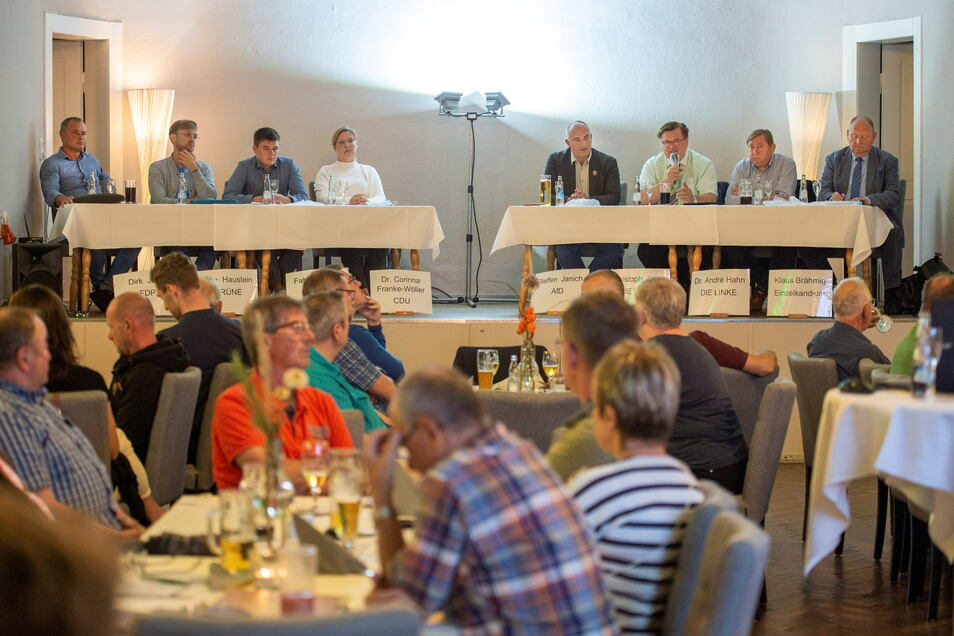 Podium bei der Bahnstrecken-Debatte in Pirna-Zuschendorf: Dirk Jahn (FDP), Nino Haustein (Grüne), Fabian Funke (SPD), Corinna Franke-Wöller (CDU), Steffen Janich (AfD), Christoph Fröse (Freie Wähler), André Hahn (Linke) und Einzelkandidat Klaus Brähmig (v